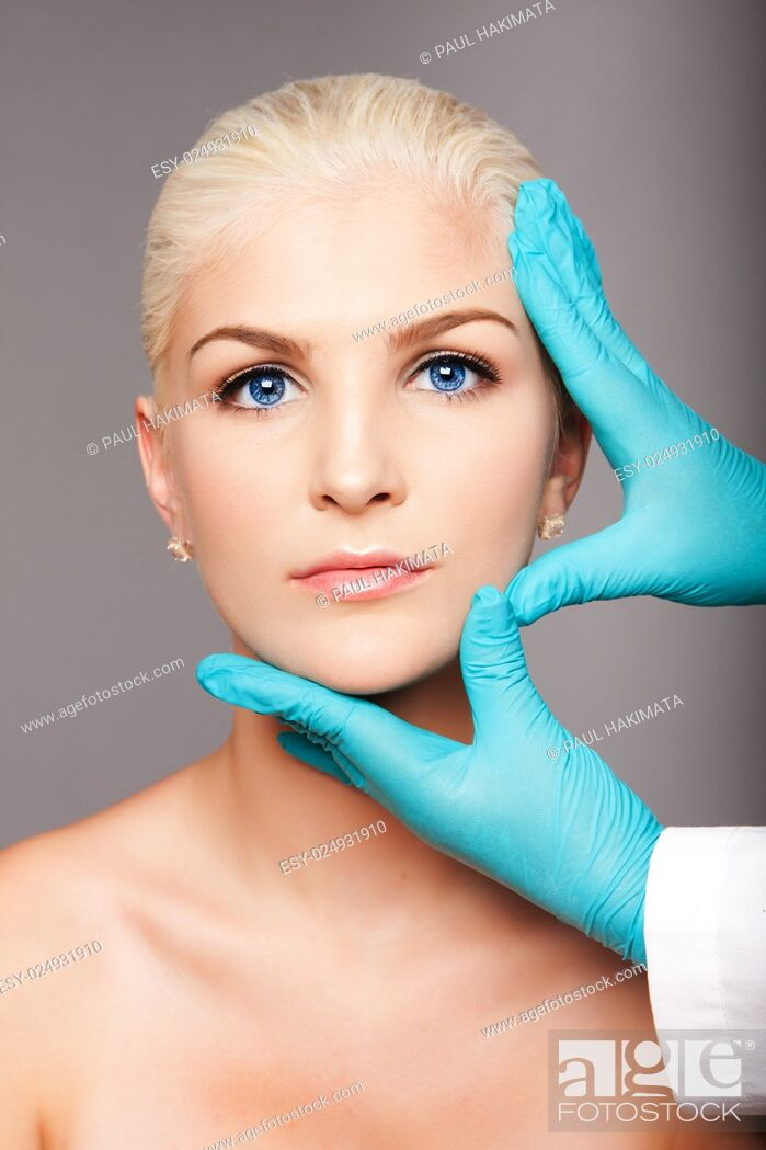 Stock Photo: Beautiful face of young woman for Aesthetics facial skincare concept touched by cosmetic plastic surgeon beautician.