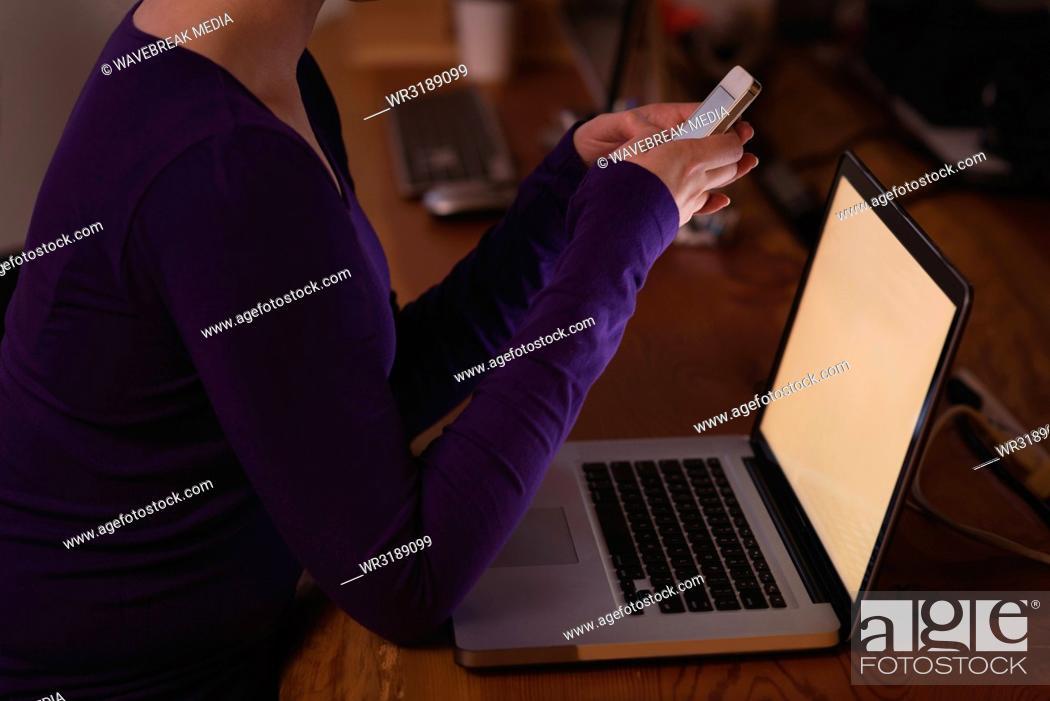 Stock Photo: Female executive using mobile phone at desk.