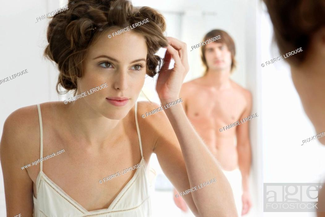 Stock Photo: Woman using curlers with her boyfriend in the background.