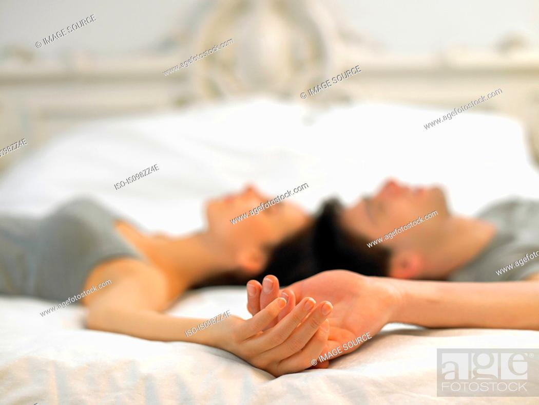 Stock Photo: Young couple lying on bed holding hands.