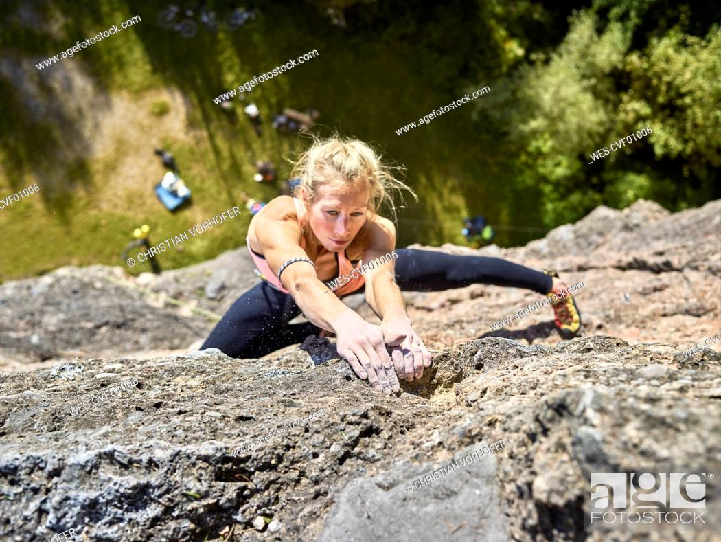 Stock Photo: Austria, Innsbruck, Hoettingen quarry, woman climbing in rock wall.