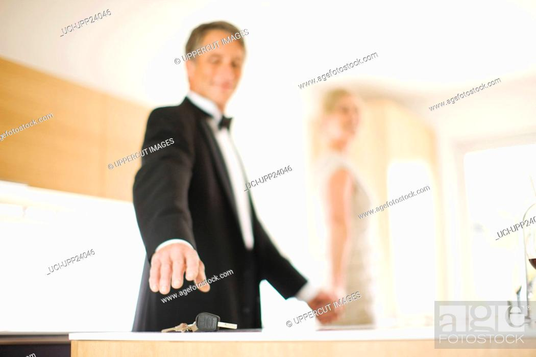 Stock Photo: Couple in eveningwear reaching for keys on kitchen counter.