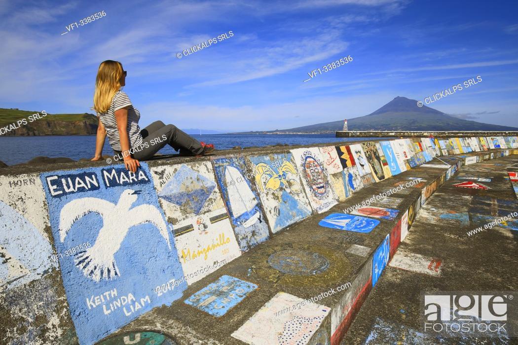 Stock Photo: Woman sitting at the port of Horta observes Pico Island, Marina da Horta, Cais de Santa Cruz, Faial, Azores, Portugal, Western Europe.