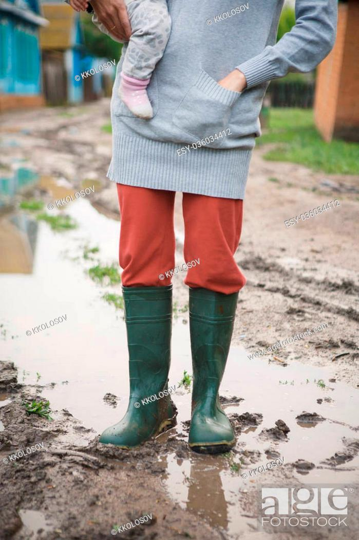 Stock Photo: woman in rubber boots with a child standing in a puddle after a summer rain in the village.