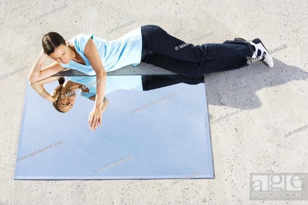 Stock Photo: Woman lying down on ground with mirror and reflection.