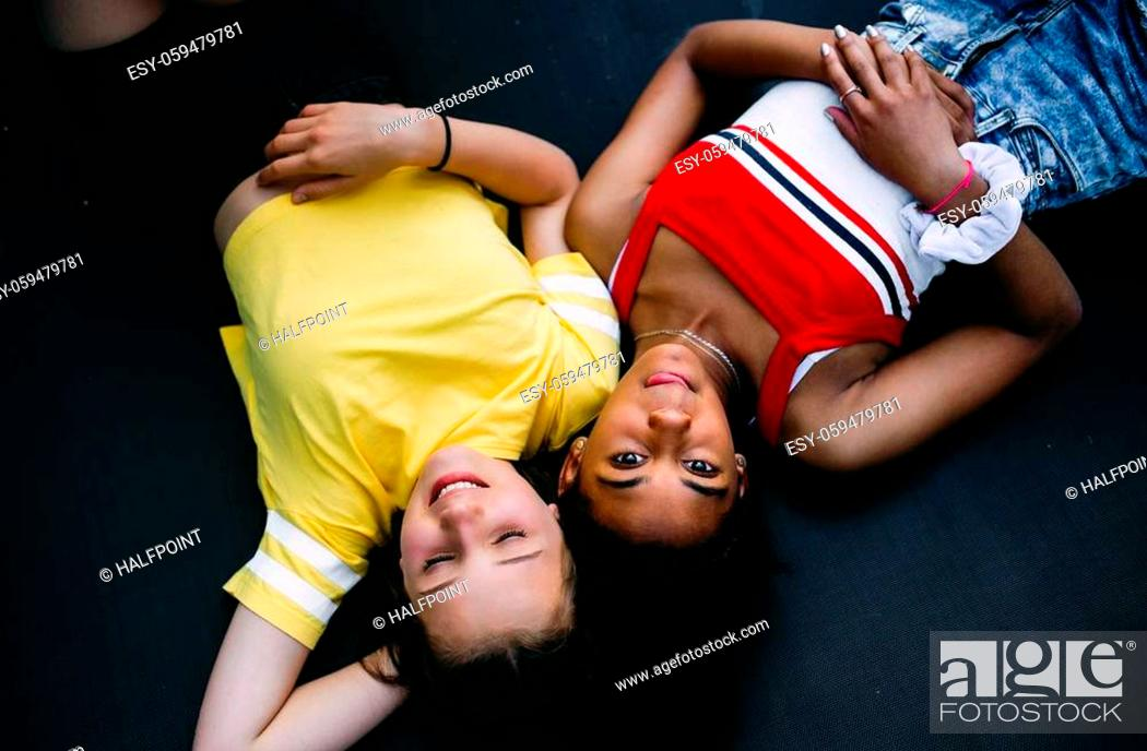 Stock Photo: Top view of cheerful young teenager girls friends outdoors in garden, looking at camera.