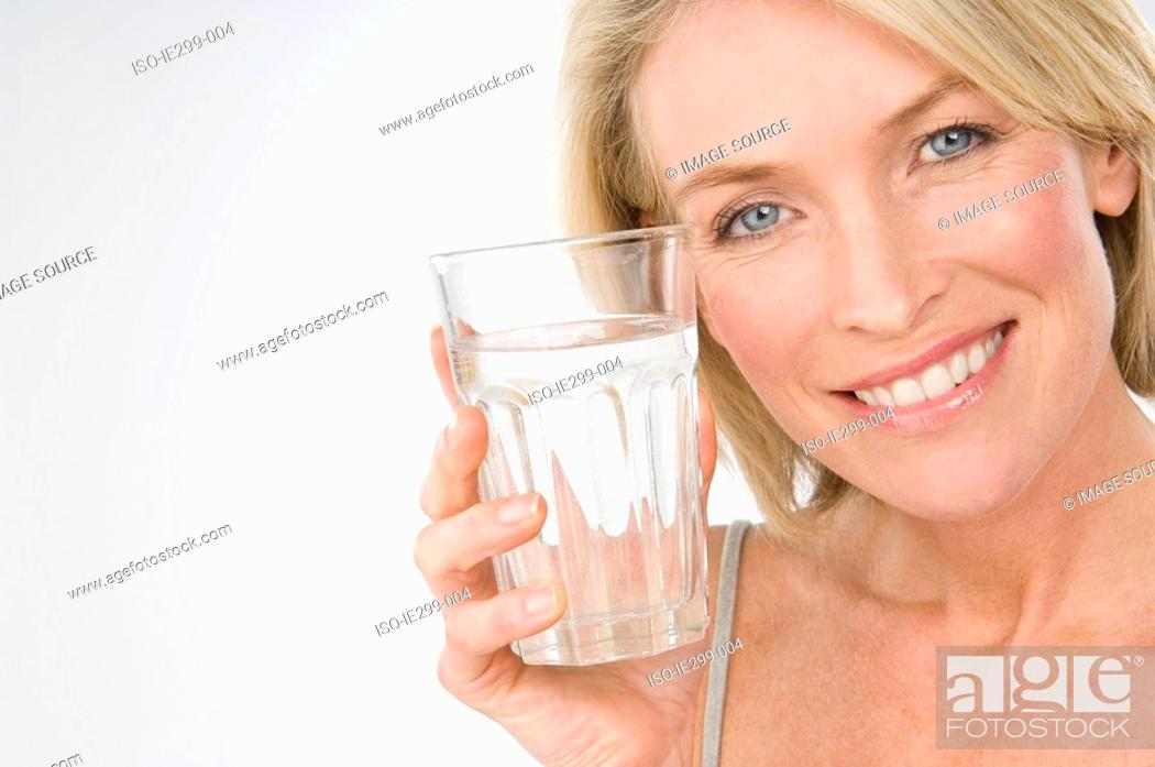 Stock Photo: A woman holding a glass of water.