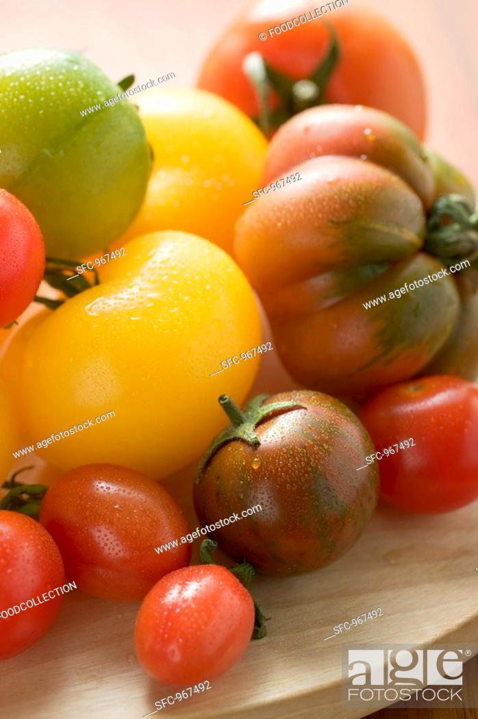 Stock Photo: Various types of tomatoes on wooden plate detail.