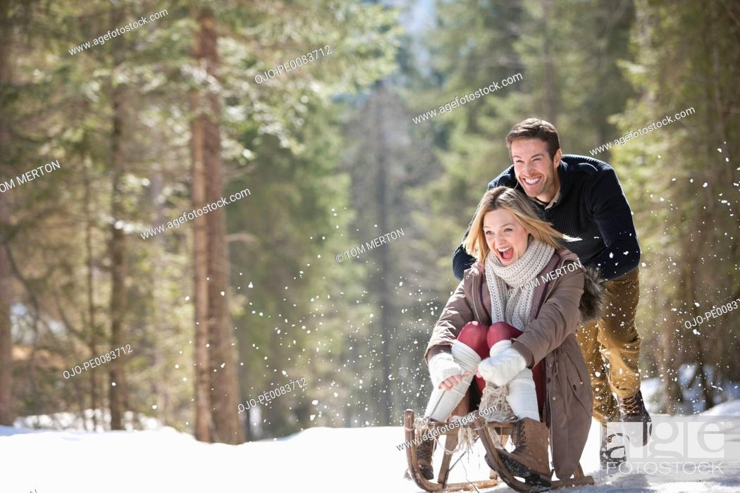 Stock Photo: Man pushing woman on sled in snowy woods.