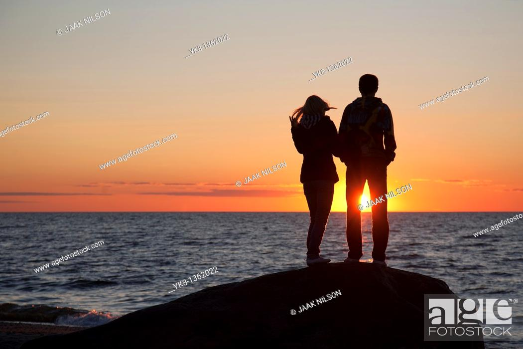 Stock Photo: Couple Silhouettes at Sunset on Beach.