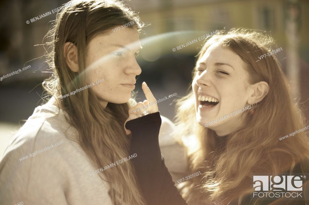 Stock Photo: couple outdoors in sunlight, joking woman touching nose of man, making fun, in Berlin, Germany.