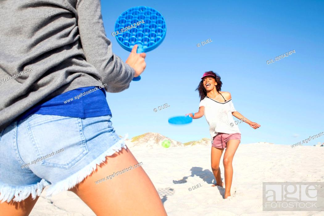 Stock Photo: Women on beach playing tennis.