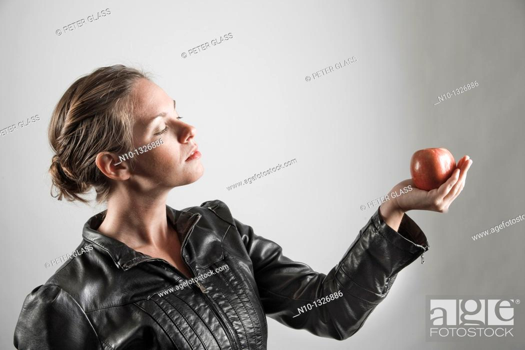 Stock Photo: Young woman holding an apple.