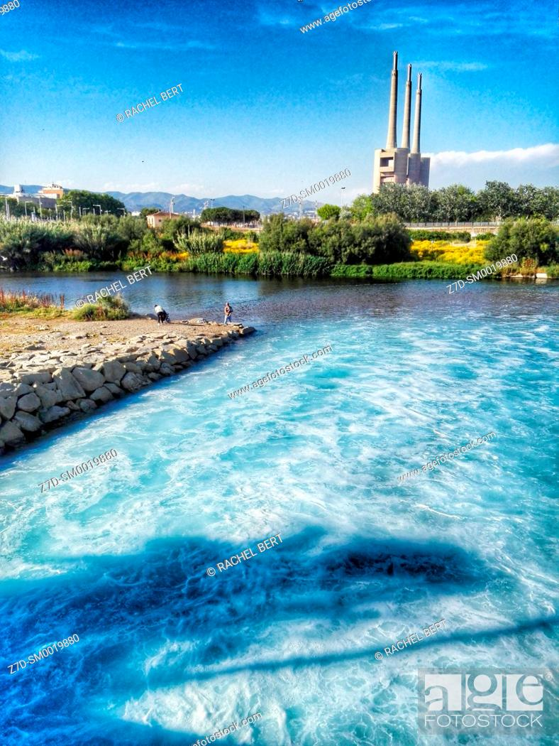 Stock Photo: Besos river, purified water from treatment plant, in the background the chimneys of the old thermal power station, Sant Adrià del Besòs, Barcelona, ??Catalonia.