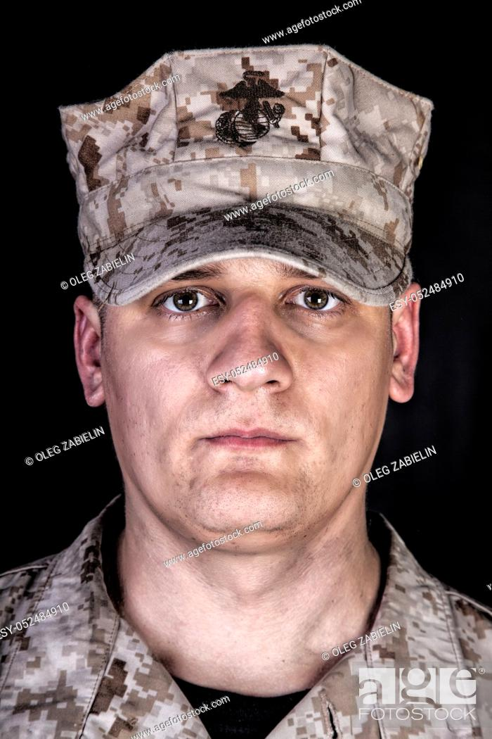 Imagen: Close up studio portrait of U. S. marines infantry soldier in camouflage combat uniform and patrol cap with United States Marine Corps emblem on it.