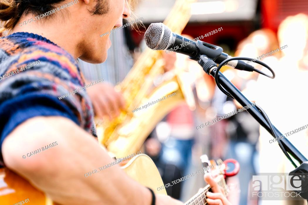 Stock Photo: Selective focus on a face of a man singing and playing a guitar in the street.