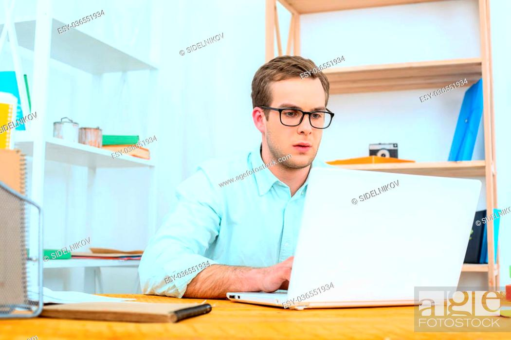Stock Photo: IT company. Young programmer working with laptop. Nice office interior. Professional coder looking at laptop.