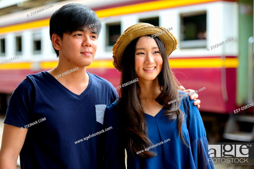 Photo de stock: Portrait of young Filipino tourist man and young Asian tourist woman together and in love at Hua Lamphong railway station.