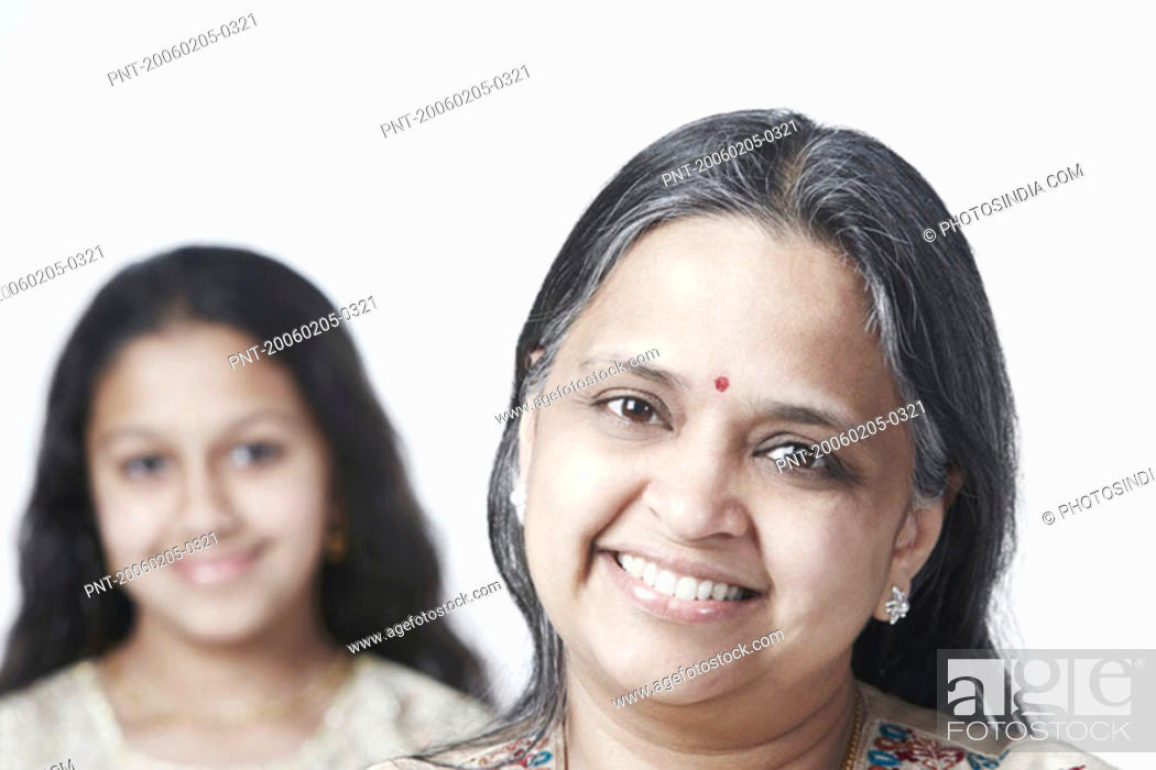 Stock Photo: Portrait of a mature woman smiling with her daughter standing behind her.