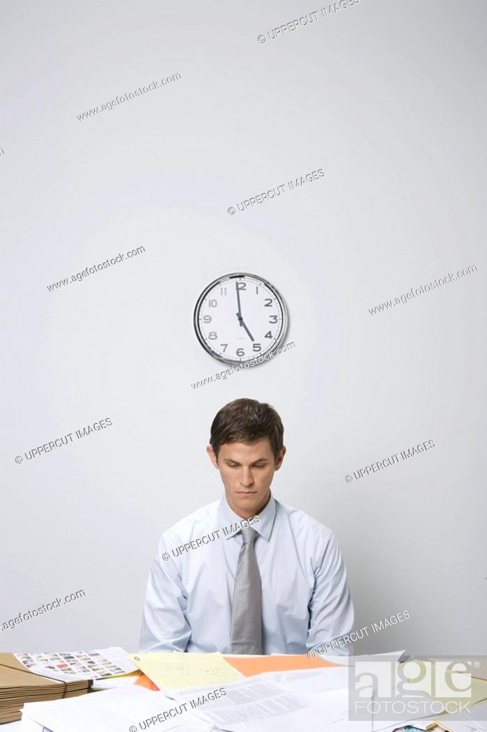 Stock Photo: Businessman at desk covered in paperwork.
