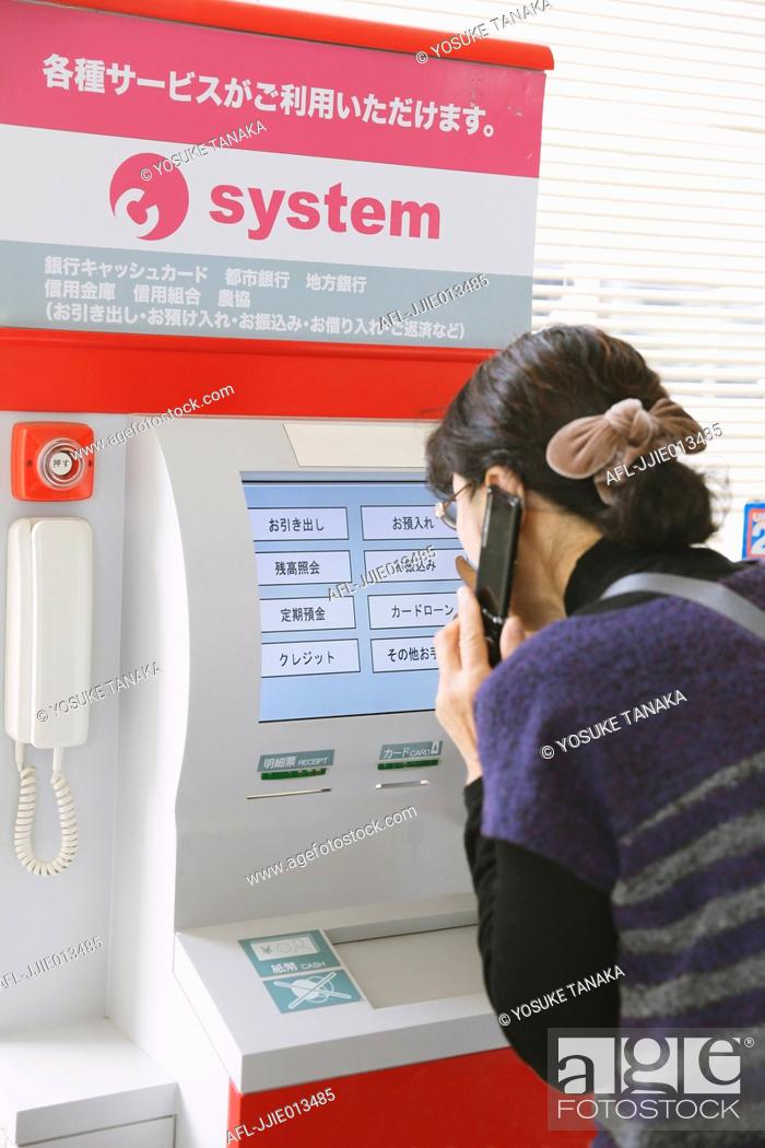 Stock Photo: Japanese woman using ATM in a convenience store.