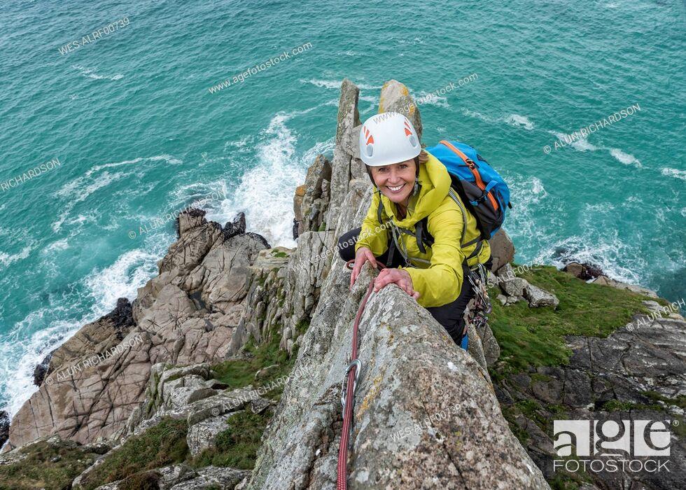 Stock Photo: UK, Cornwall, smiling woman climbing on Commando Ridge.