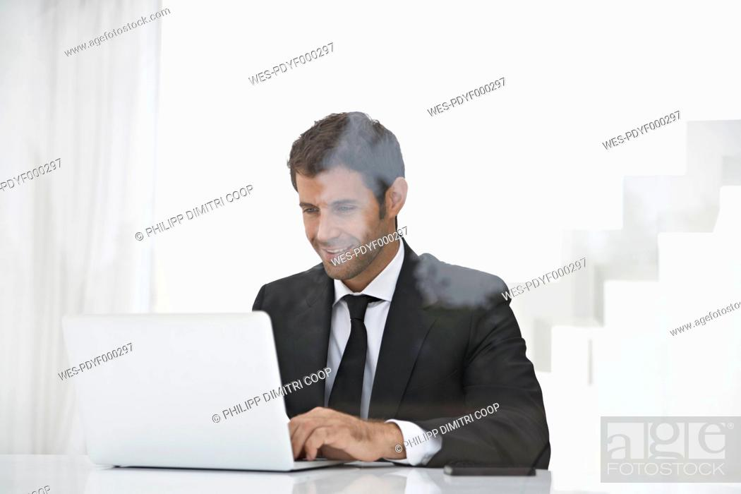 Stock Photo: Spain, Businessman using laptop, smiling.