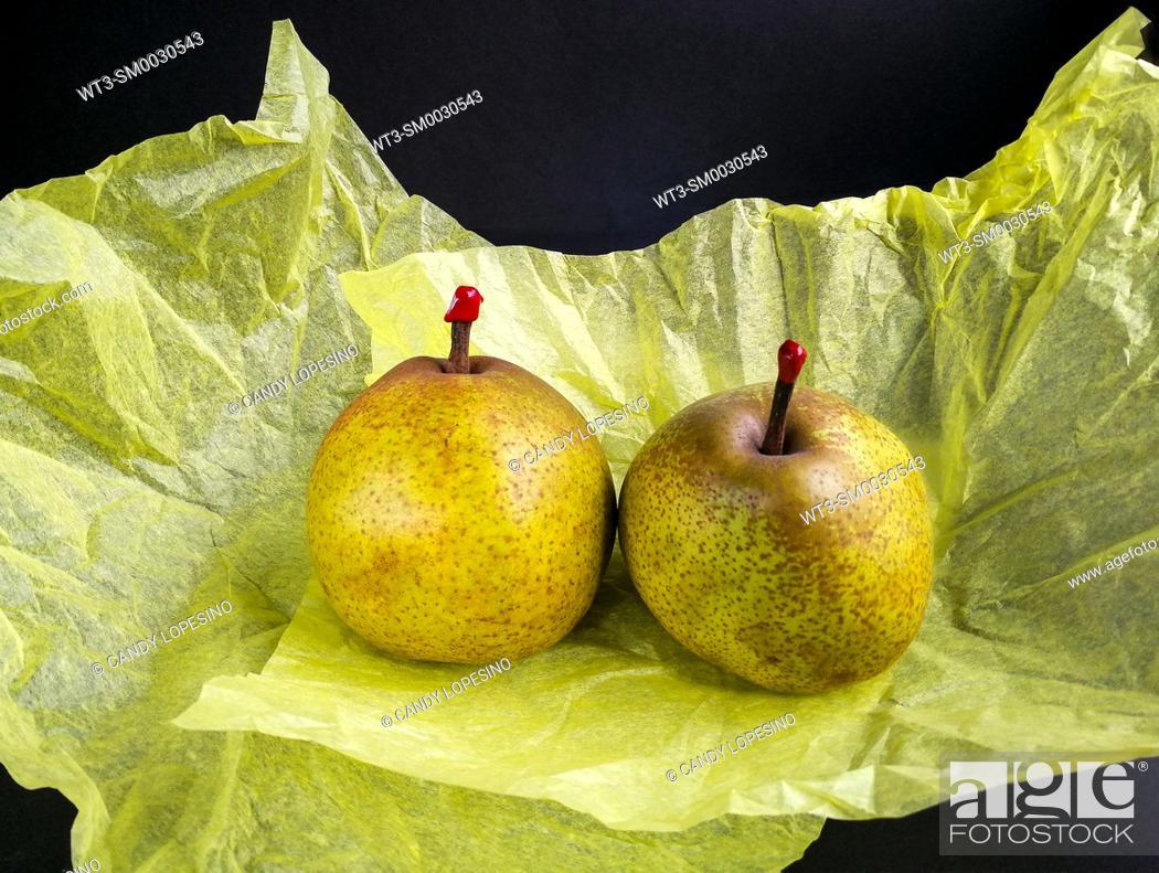Stock Photo: Two Passa Crassana pears on yellow silk paper on black background.