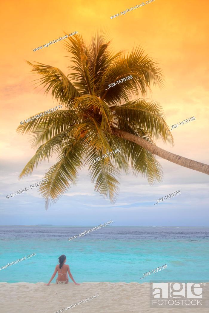 Stock Photo: Girl seated under a palm on seashore, Biyadhoo island, Maldives.