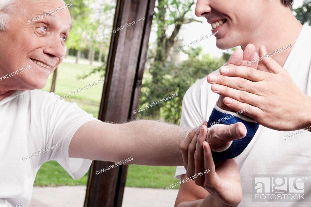 Imagen: Physiotherapist examining a man's hand.