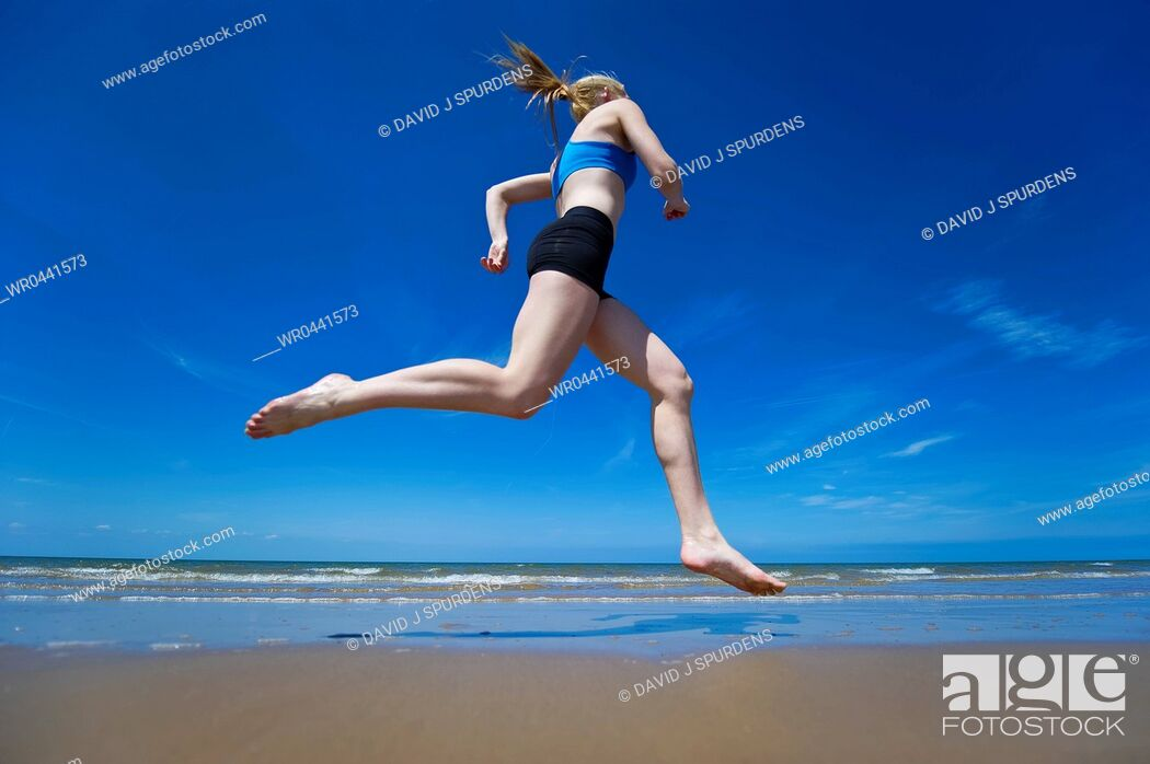 Stock Photo: An athletic runner jogging along a sandy beach at the oceans edge.