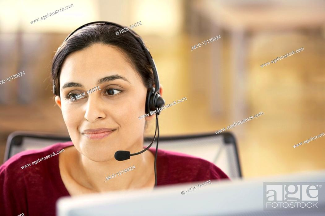 Stock Photo: Mid-adult female office worker sitting in cubicle wearing headset portrait.