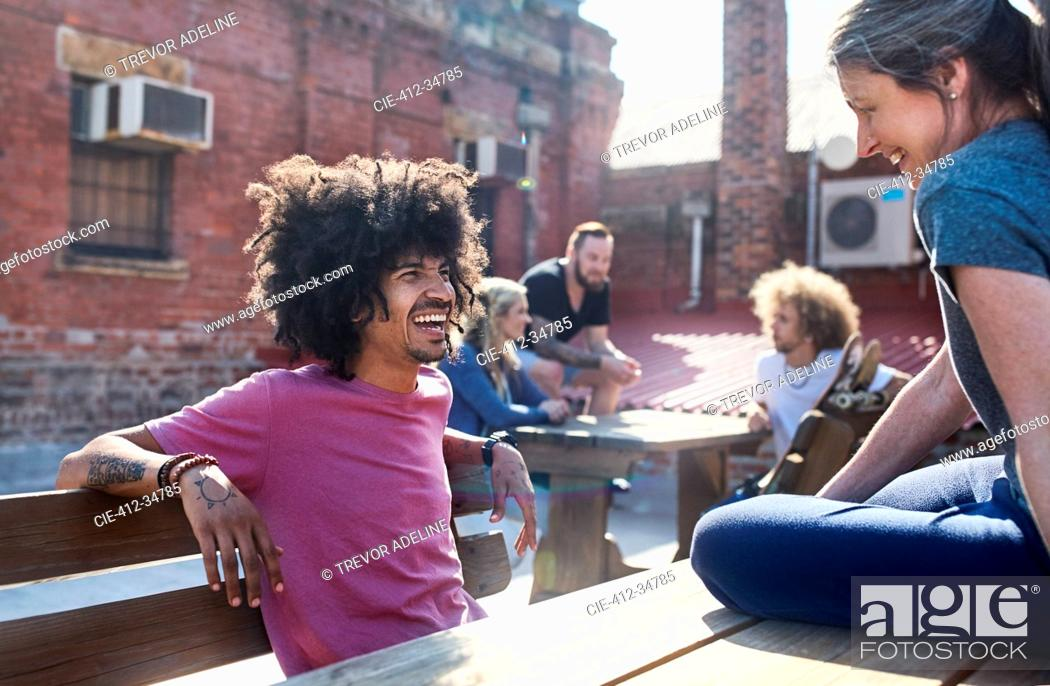 Stock Photo: Smiling friends hanging out talking on sunny urban rooftop.