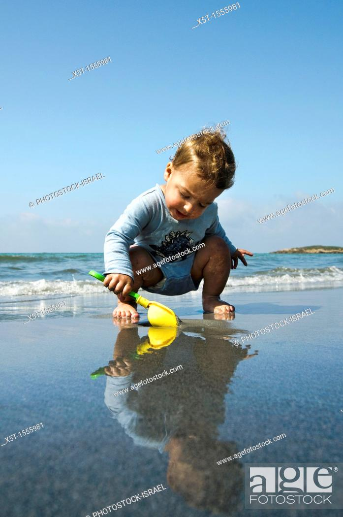Stock Photo: Two year baby boy plays on the beach.