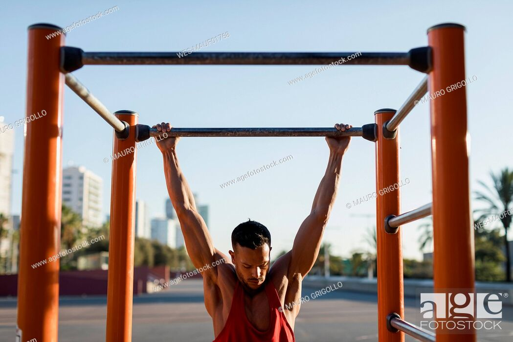Stock Photo: Fit man working out in climbing parcour, doing pull ups.