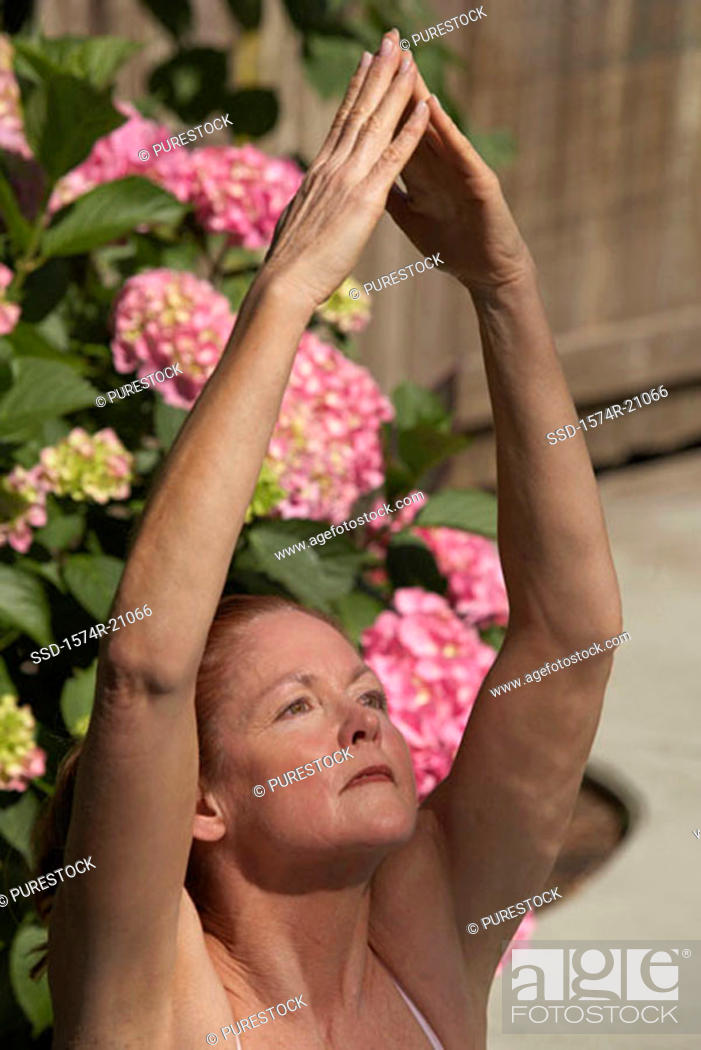 Stock Photo: Close-up of a mature woman meditating in a tree pose.
