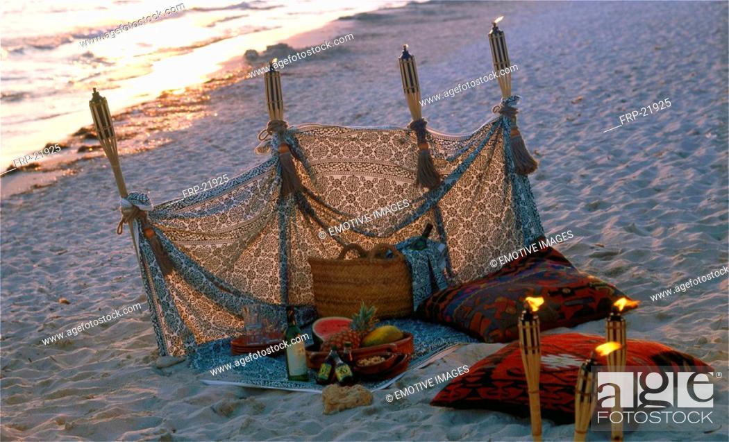 Stock Photo: Twilight on the beach: windbreak and torches.