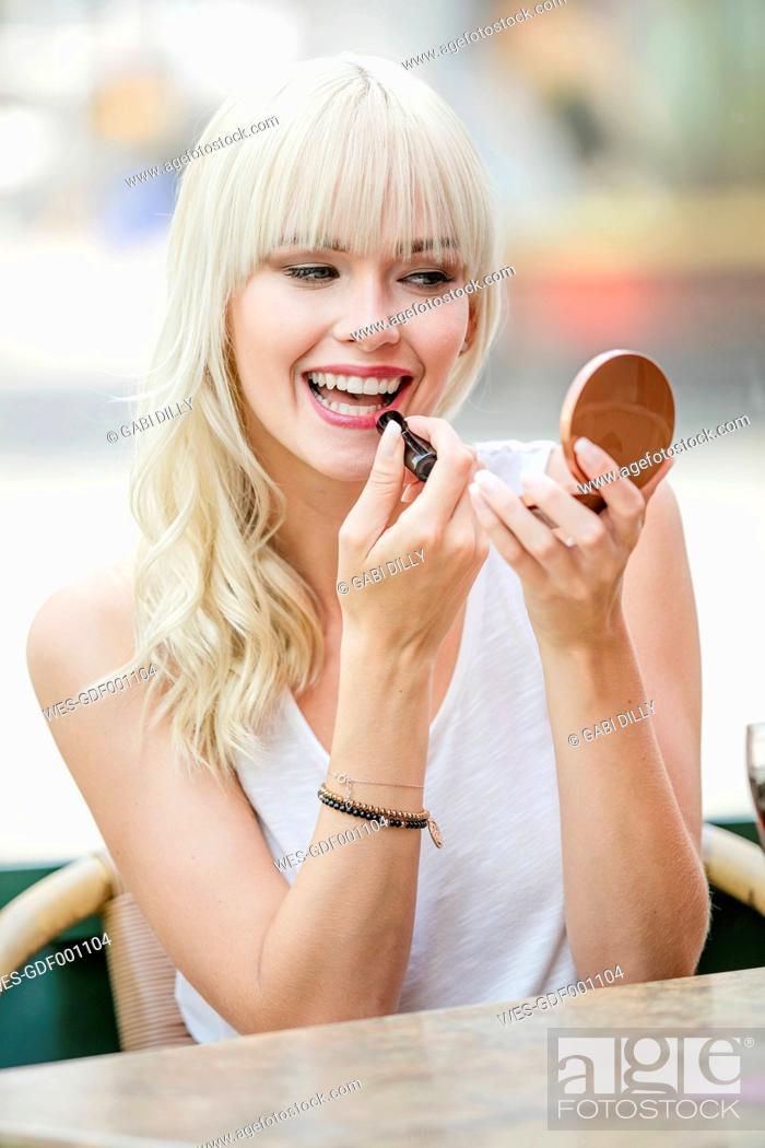 Stock Photo: Portrait of blond woman sitting at sidewalk cafe applying lipstick.