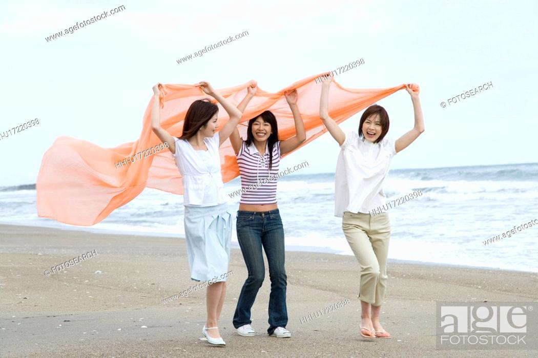 Stock Photo: Three young women at beach, holding a shawl in the air, side view.