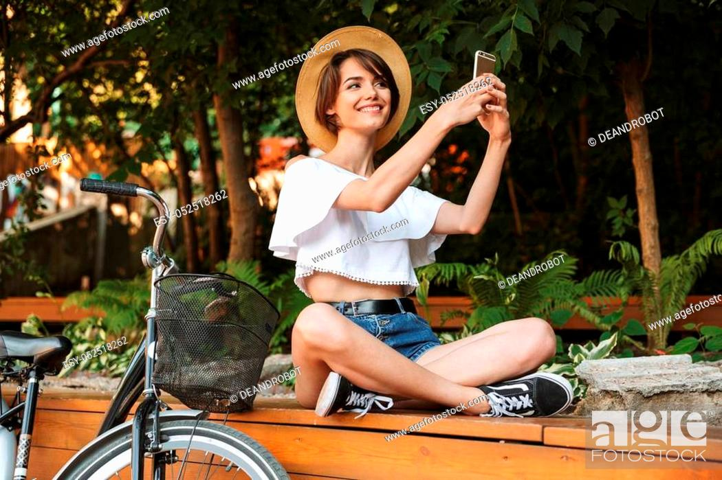 Stock Photo: Smiling young girl in summer clothes sitting at the park with bicycle and taking selfie with mobile phone.