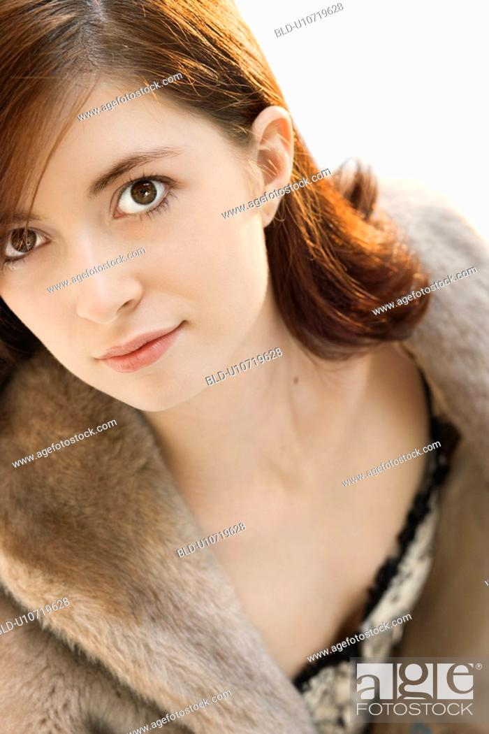 Stock Photo: Head and shoulder portrait of attractive young redhead Caucasian woman.
