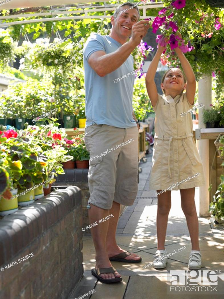 Stock Photo: Father and daughter looking at a hanging basket.