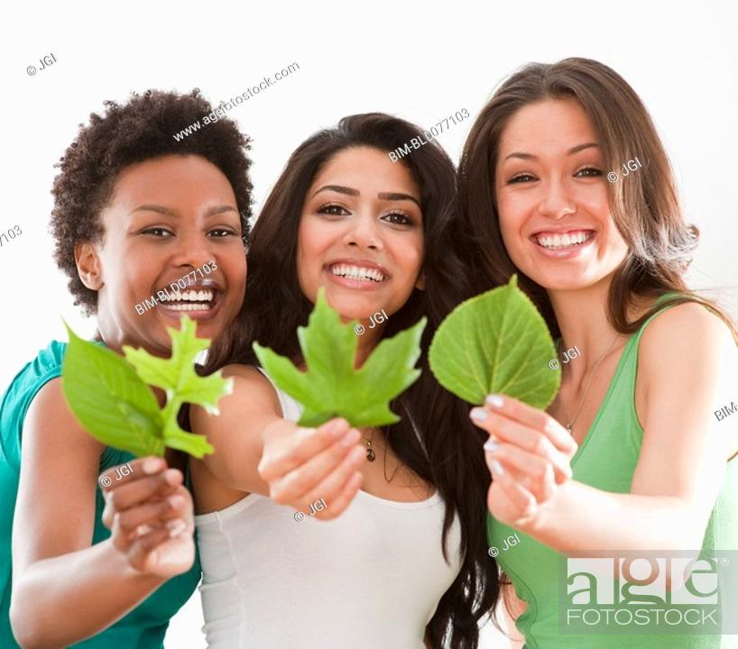 Stock Photo: Friends holding out fresh, green leaves.