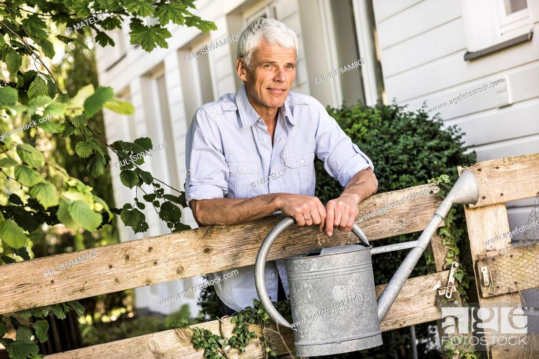 Stock Photo: Mature man with watering can in garden.