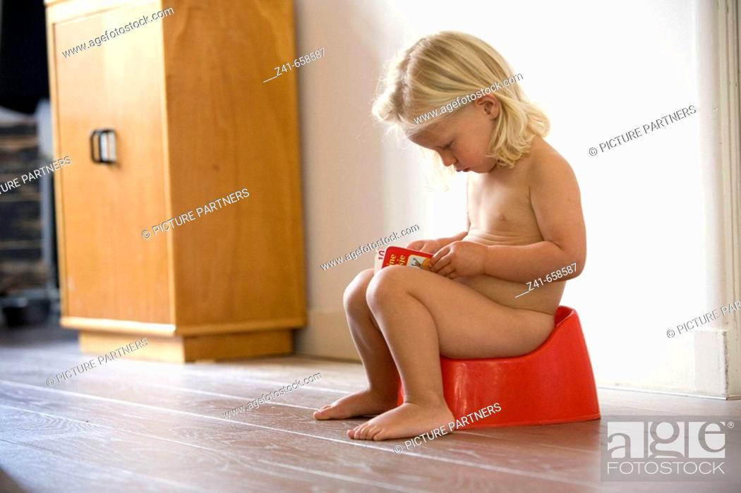 Stock Photo: Blond little girl is sitting on a potty.