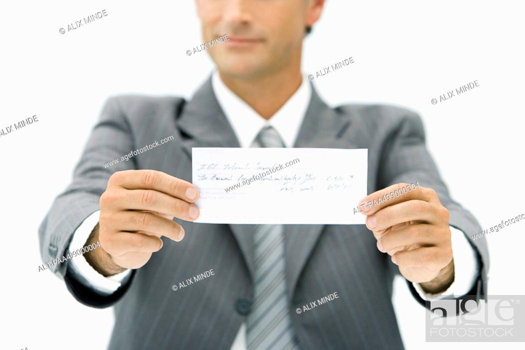 Stock Photo: Businessman holding out check, cropped view.