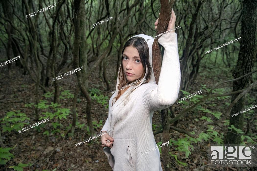 Photo de stock: Close-up of attractive woman wearing white hoodie in mysterious forest - North Carolina, USA.