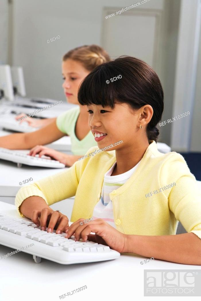 Stock Photo: Two school children 10-13 using computers in classroom.