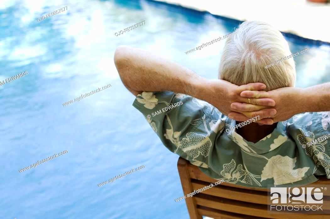Stock Photo: Man sitting by pool relaxing.