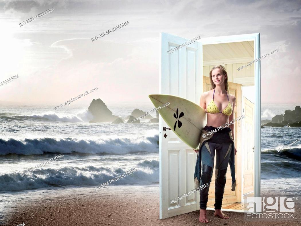Stock Photo: Woman emerging from door on beach.